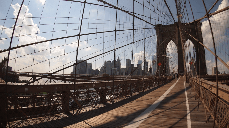 Explore NYC like a local by walking the iconic Brooklyn Bridge. Image taken from the central point of the bridge, surrounded by the wires that suspend it with New York City in the distance