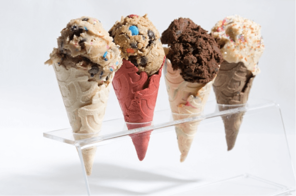 One of the best Things To Do in New York is to indulge in the latest fad - pictured here are 4 waffle ice cream cones standing in a clear perspex display stand, each with different ice cream flavours including cookie dough, chocolate chip and penut butter