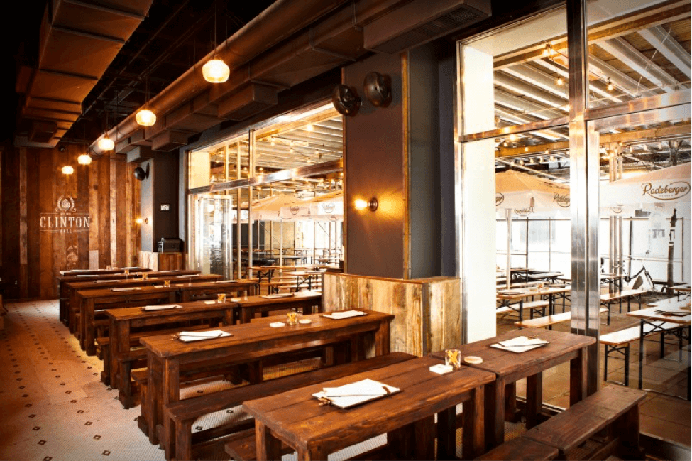 Photograph of the inside of an emplty restaurant with dark wooden tables and bench seats lining the side nearest, separated by a glass wall where there are lighter wooden tables and bench seats with metal legs
