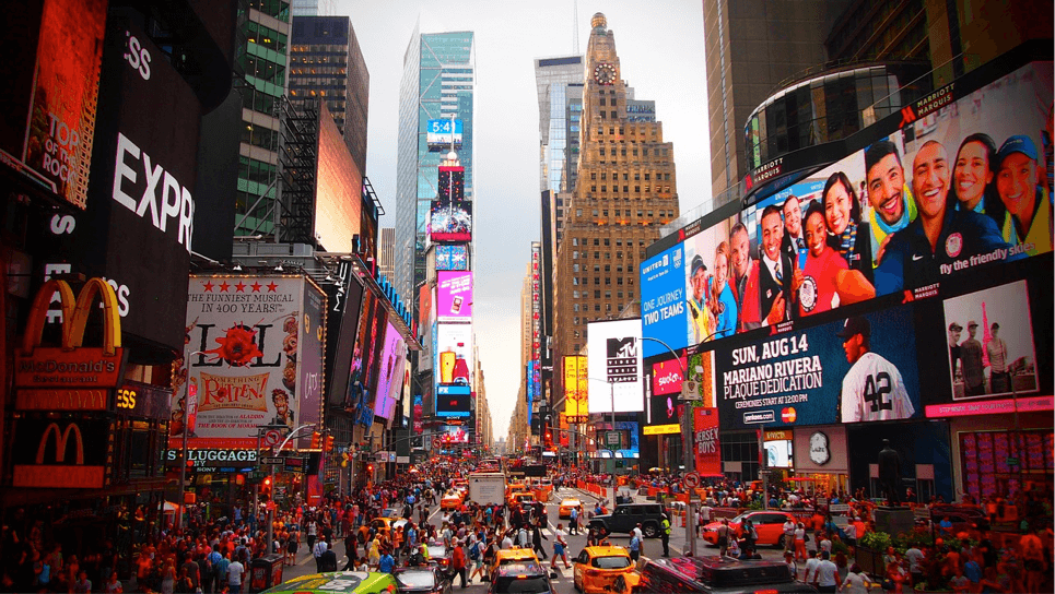 Elevated shot of Time Square in New York with neon advertisements either side of the street, masses of people walking in both directions and across the zebra crossing. In the foreground there are two new york taxi cabs waiting at the crossing. This vibrant scene makes it one of the best things to do in New York City.
