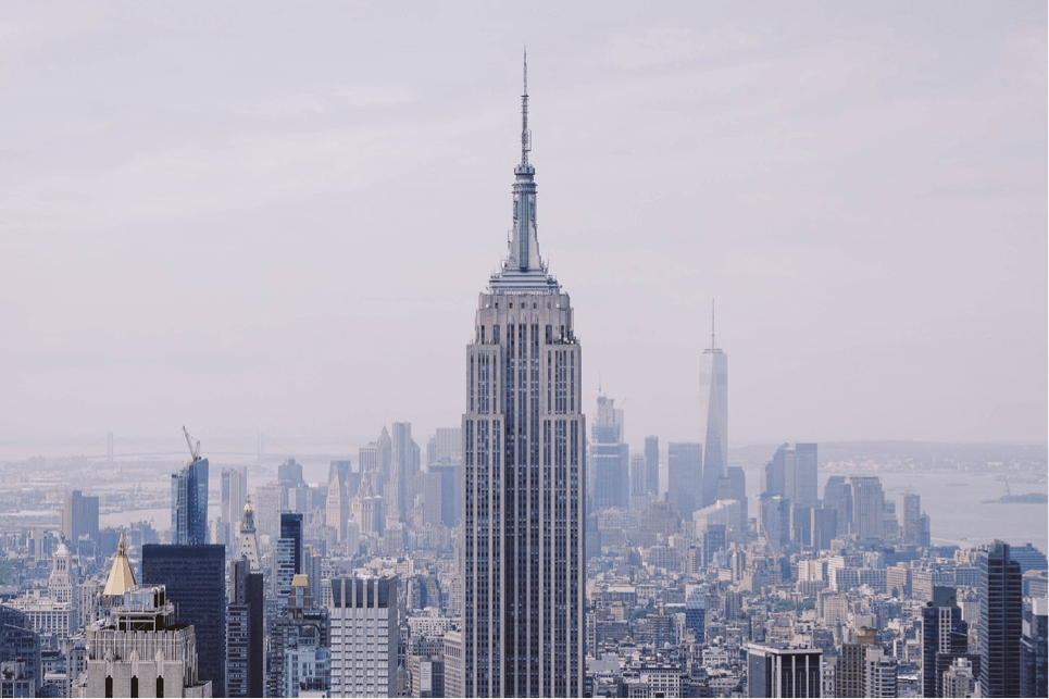 If you are wondering what to do in NYC, seeing the skyline from above is it. This is a shot of the empire state building taking from top of the rock observatory with a view over the rest of new york. Sky has a purple tinged haze, photograph was taken at dusk.