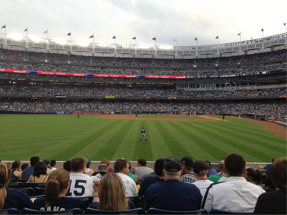 One of the best Things To Do in NYC is see a sporting event - this photo is of a Baseball Stadium from the lower stands with 7 rows of people sat in front, the ball game in the middle and full stands behind the game