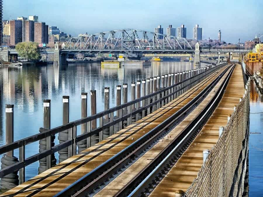 View from the train tracks in the Bronx looking back towards New York City. Train tracks in the forground next to the river, brige over the river in the middle of the image and skyscrapers in the distance behind them
