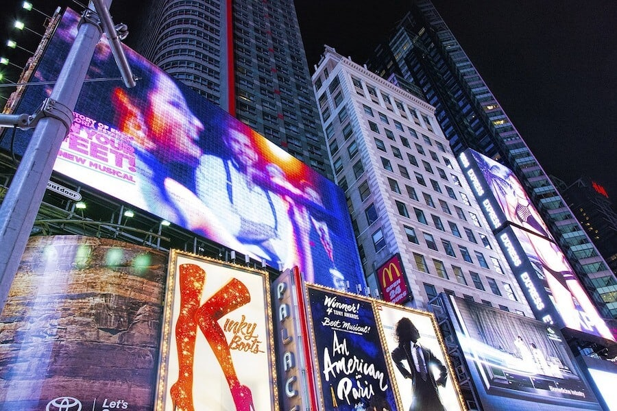 When wondering what to do in New York, seeing a show is a no brainer. Close up shot of Time Square from ground level looking up at the illuminated billboards advertising the Palace Theater, The Shows Kinky Boots and An American in Paris