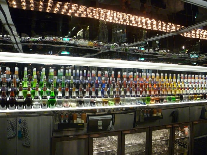 Bar Area in House of Bols Museum with mirrored back bar with lines of coulourful cocktail liquers lined up in front of it