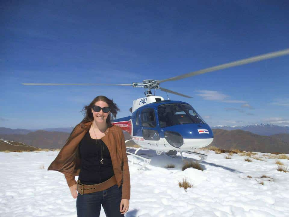Vicki in front of a helicopter on top of a snowy mountain