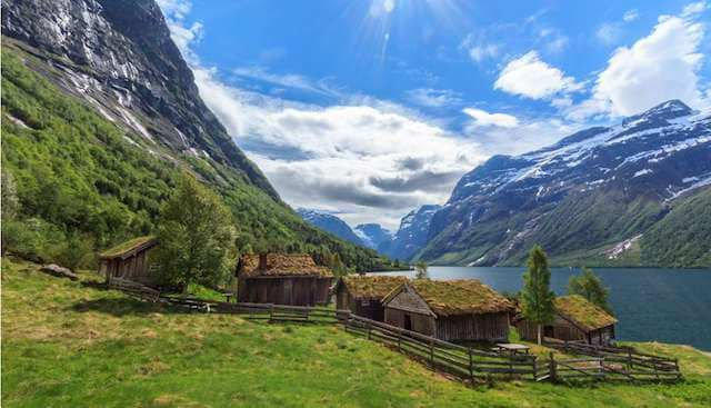 Loden Valley in Norway with 3 wooden houses in the foreground and lake, mountains and white clouds in the background