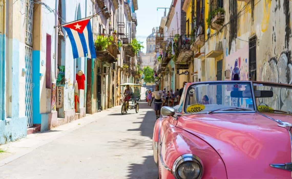 Old Pink Cadillac parked at the front right of the shot on a quite Cuban street with the Cuban flag draped from a balcony in the background