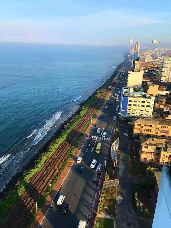 Colombo from above with the city on one side, road down the middle next to train tracks and the ocean on the left.