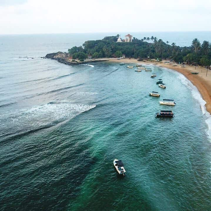 Unawatuna - beautiful beach in Sri Lanka, turquoise water in the foreground with boats lined up along the shore line, the beach curves round to the back of the image, behind which is a mount covered in plam trees among which you can see the white Pagoda and Big Buddha temple.