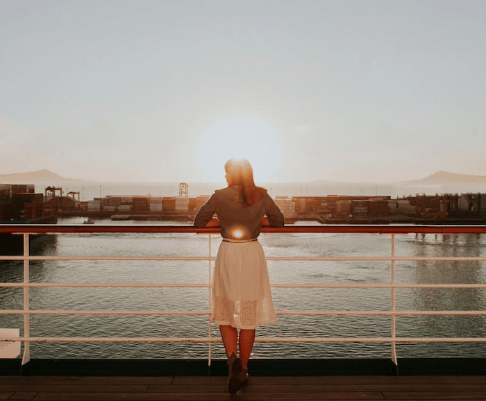 woman stood on a cruise ship balcony for Solo travel on a cruise