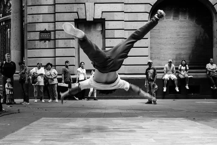 Black and white photographer of an acrobat on the street in mid-air