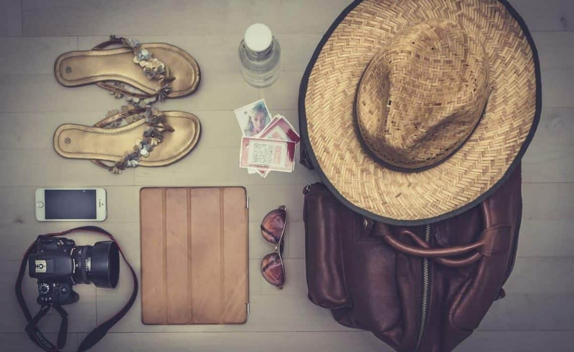 Cruise Packing List flatlay - camera, hat, suitcase and flip flops