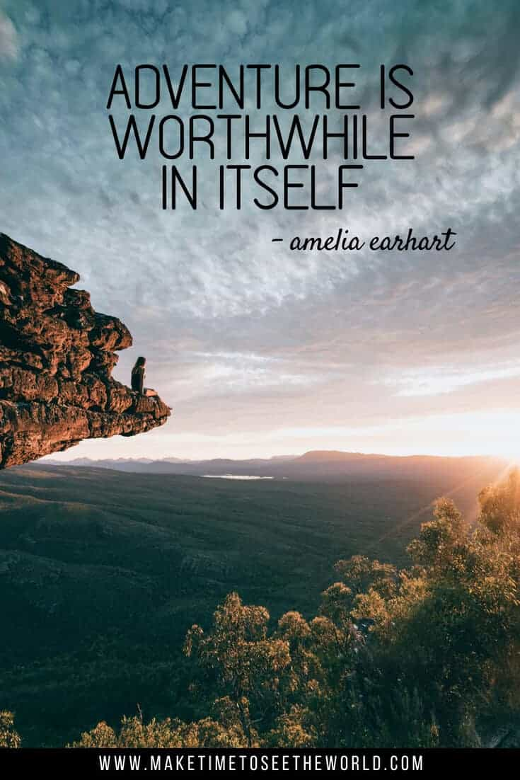Adventure is Worthwhile in itself - a quote about adventure pin image of a woman sat on a high rocky outcrop overlooking a national park just after sunsrise
