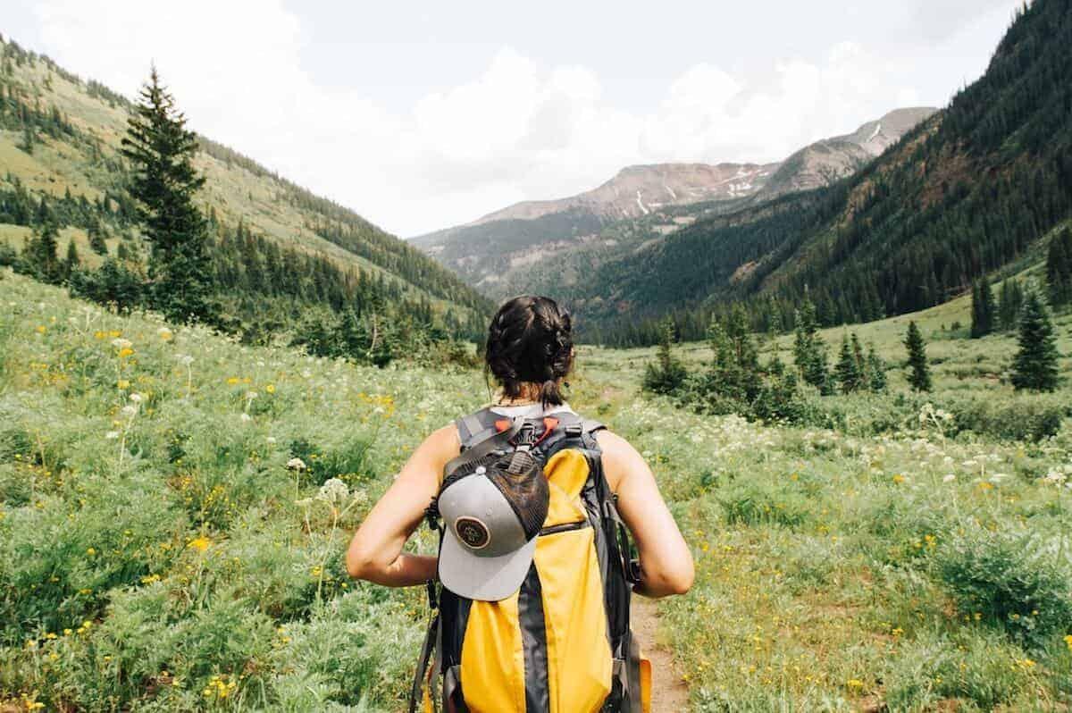 Cadeaux écologiques pour le voyage - femme voyageant à travers un champ vert portant un sac à dos