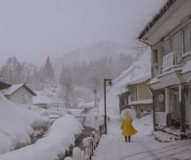 Man in Yellow coat with clear umbrella walking down a shony street next to a river in Ginzan Onsen