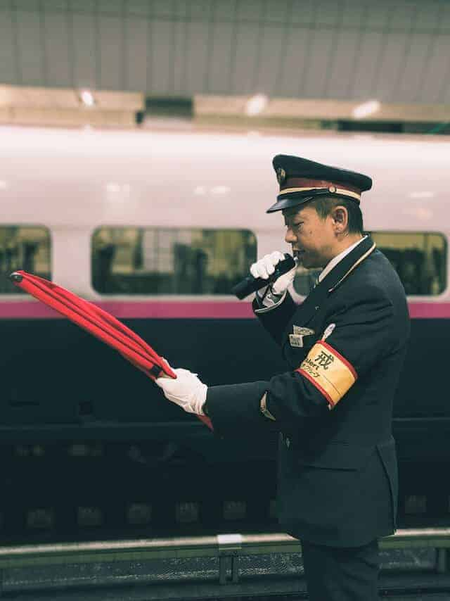 Conductor at Tokyo Train Station announcing the approaching train with a red clipboard