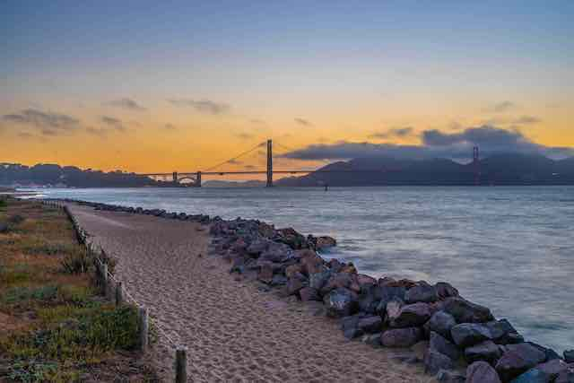 Pathway next to the water in Crissy Field San Francisco with view of the Golden Gate Bridge and sunset in the background