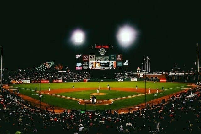 View of the field at Oracle Park at night with the scoreboard flanked by two floodlights which are turned on