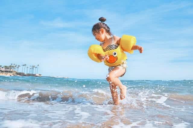 Kid wearing floaties paddling at the beach