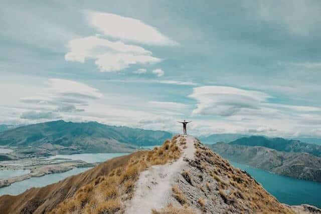 Person standing with open arms at Roy's Peak Lookout, New Zealand