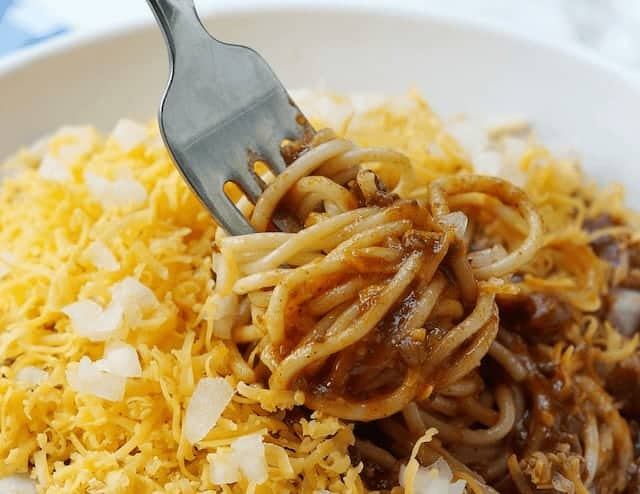 Cincinatti Chilli - spaghetti covered in mince, shredded cheese and onions with a fork twirling the spaghetti