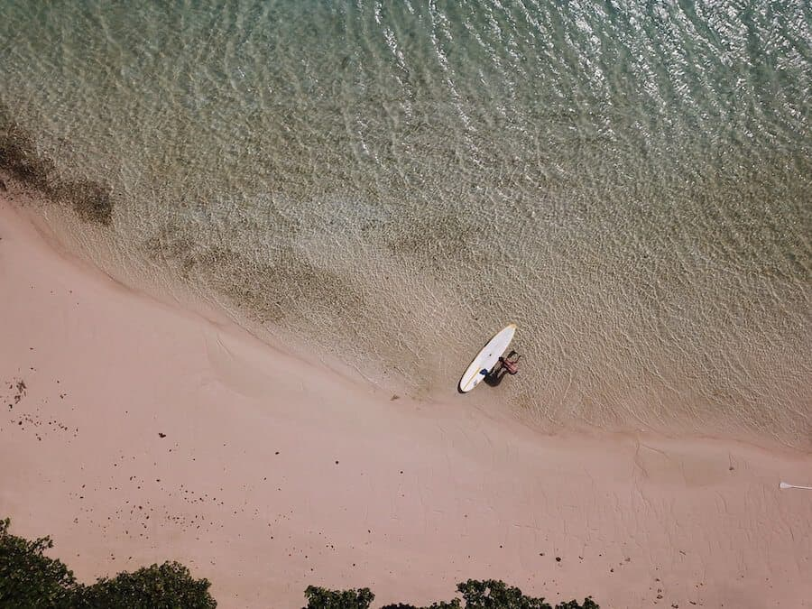 Top down aerial shot of a paddleboard at the waters edge next to pink sand