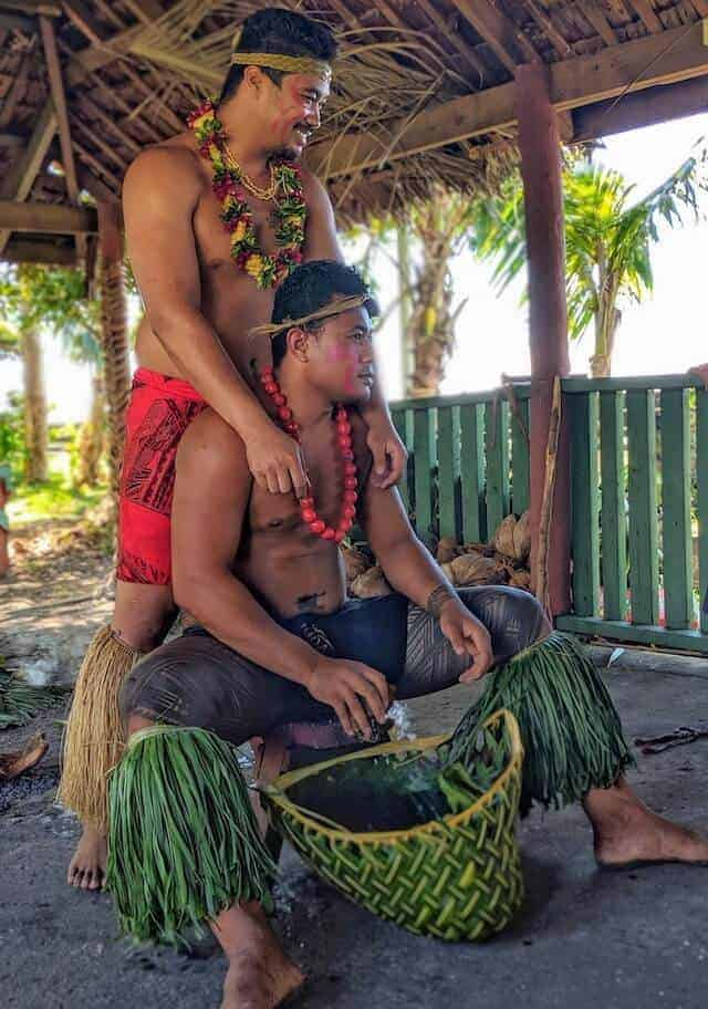 Two men dressed in traditional Samoan outfits, one whose body has the male traditional tatoo