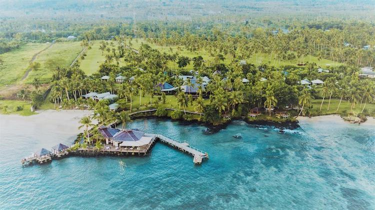 Areial View of Sinalei Reef Resort & Spa with ocean in the foreground, resort on the edge of the water and lush green palm tress behind