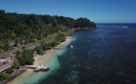 Samoa Accommodation Guide cover photo - drone shot above a hotel located next to the ocean along the coast line