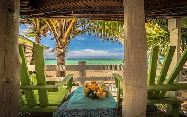 Looking out to the ocean from inside a beach Fale with green deck chairs either side of the frame