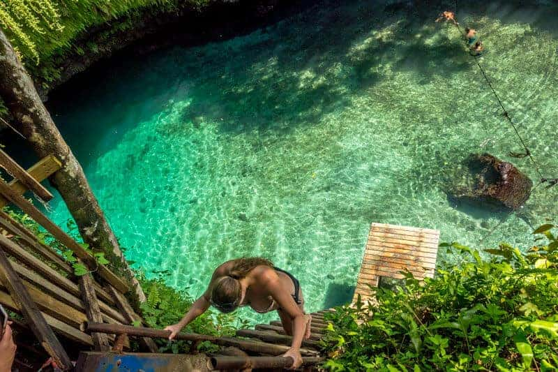 To Sua Ocean Trench from above with woman climbing down the wooden ladder in a bikini