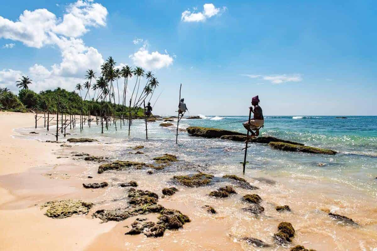 2 week Sri Lanka Itinerary Cover Photo - stilt fisherman on a beach with bright blue sky