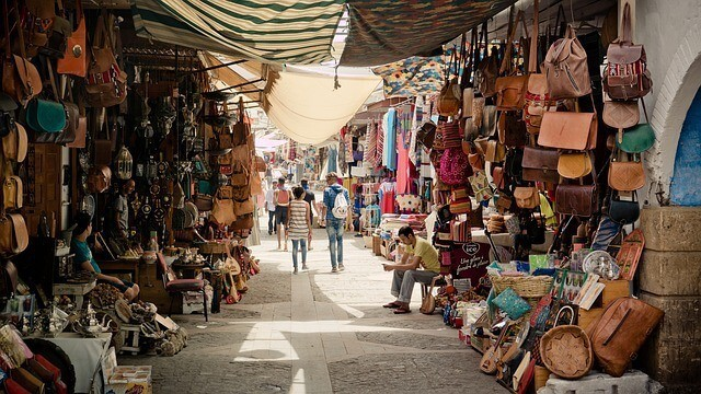 Inside the souk in marrakech with traders stalls either side of the frame and people walking away down the center