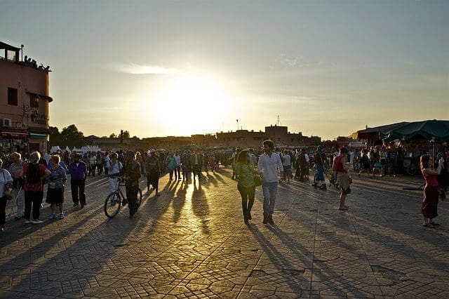 Jemaa el fna at dusk with the sun setting behind people walking towards the camera