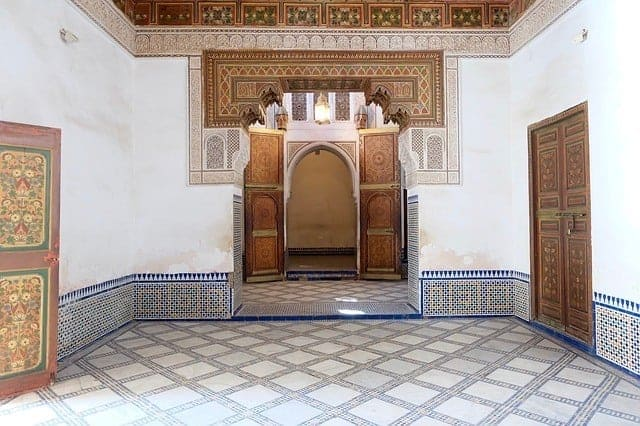 A room in the Bahia Palace with a tiled mosaic floor and ceiling, wooden doors in a traditional arched frame
