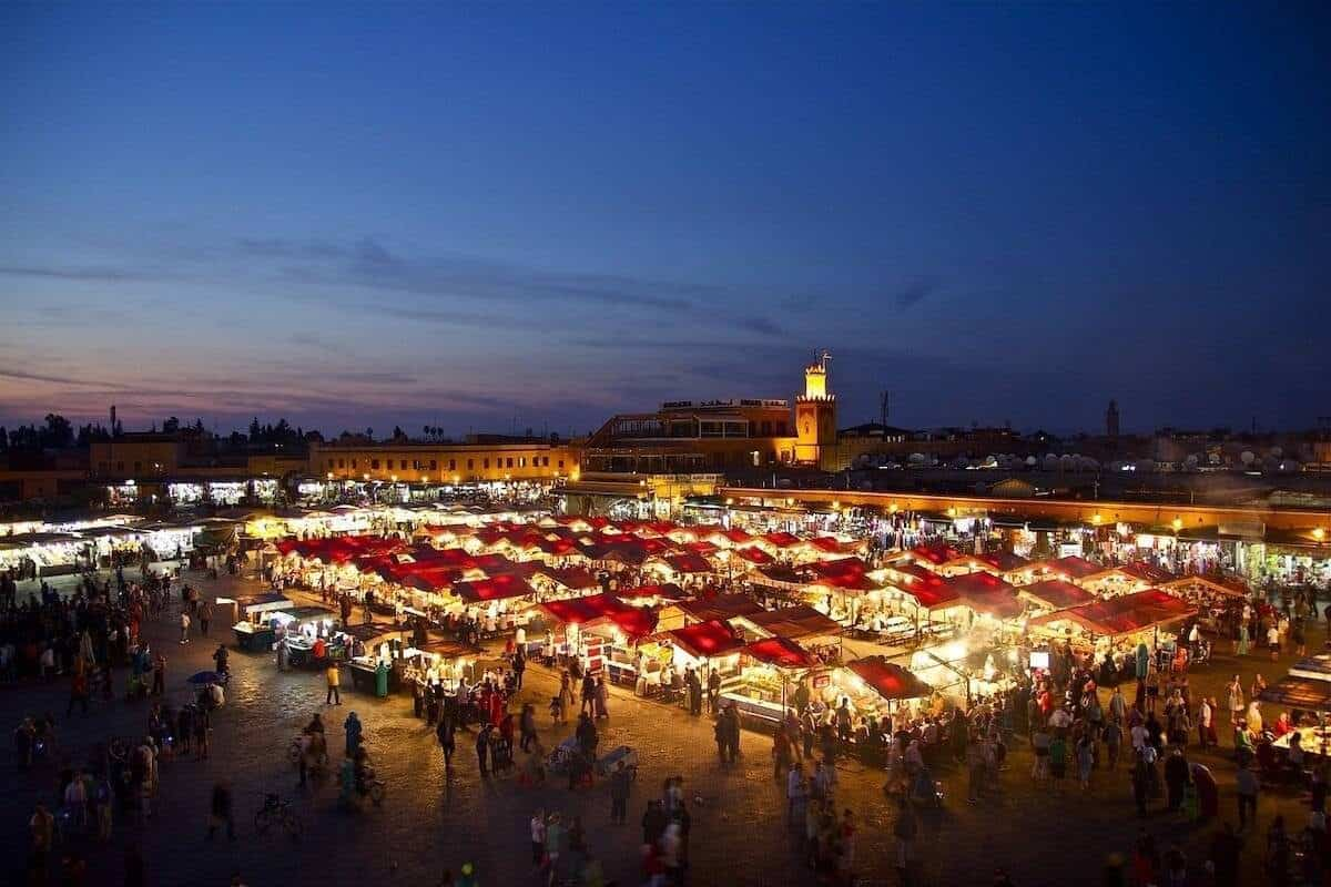 Things to do in Marrakech header image - view over the market square at night with the tents lit up and surrounded by people