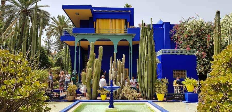 Striking blue building with contrasting yellow curtains in the upstairs windows and surrounded by exotic plants with a small blue fountain in the foreground