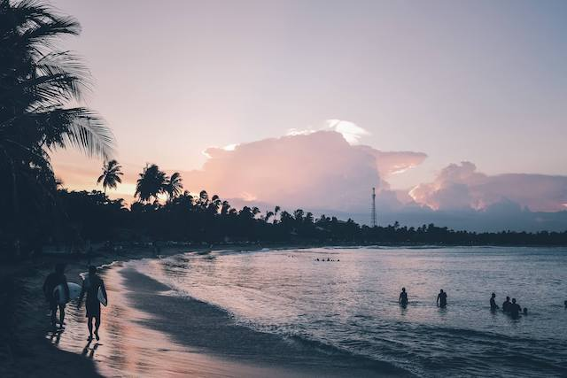Dusk at Aragum Bay in Sri Lanka with purply pink skies, six people in shaddow in the ocean , two surfers with surf boards walking towards the camera and fluffy clouds in the sky