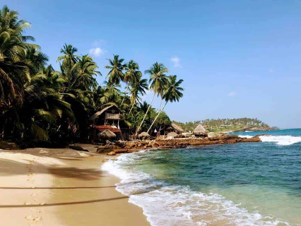 Best Beaches in Sri Lanka cover image of golden sands backed by palm tress and small waves lapping onto the sand from the right edge of the image; In the distance is a raised rock wall with two wooden huts on top