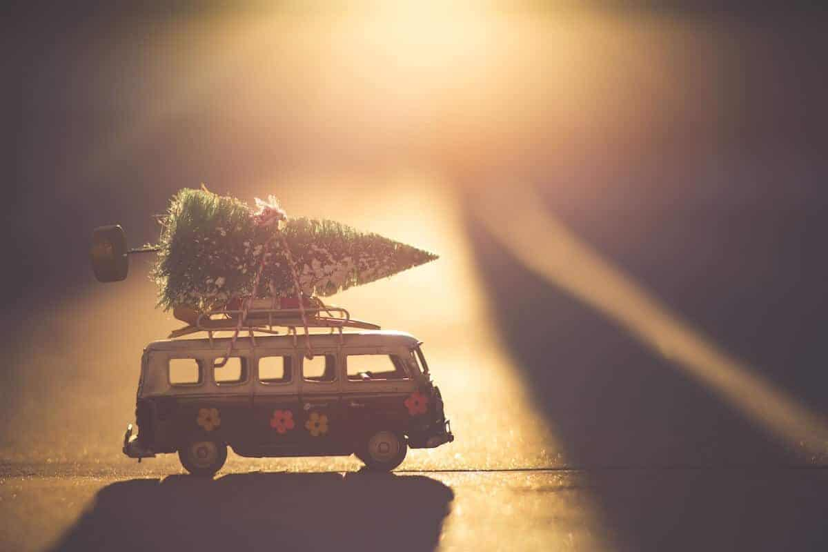 Cover photo of the best white elephant gifts for travel lovers featuring a mini vw campervan with a christmas tree on top bathed in a golden light from a sun set at the back of the shot