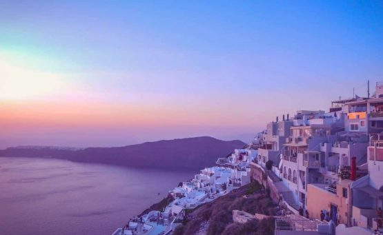 Cover photo for the Greek Island Hopping Itinerary and Travel Guide featuring a purple and pink sunset over a hillside village in Greece with the ocean below and mountains in the distance