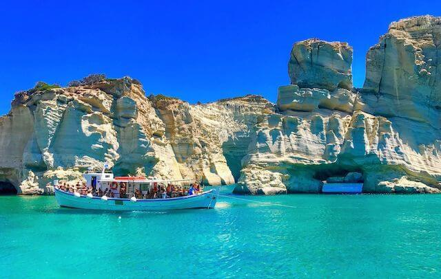 A small tourism boat packed with people sails on turquoise blue waters in front of a rugged rock face stretching the width of the shot in Milos