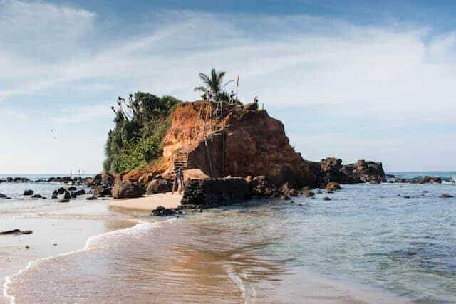 Mirissa Beach in Sri Lanka - prominent rocky outcrop in the centre of the frame with waves lapping around from each side. On the top of the large rock is a green plam tree, and the left side is completely covered with green climing plants