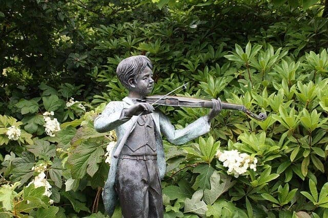 Sculpture of a boy playing a violin surrounded by lush greenery on Mount Macedon in Victoria