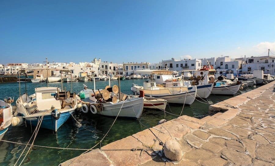 small fishing boats tied up along the harbour wall of Paros Naxos with the water behind stretching to the buildings on the shore on the other side of the marina