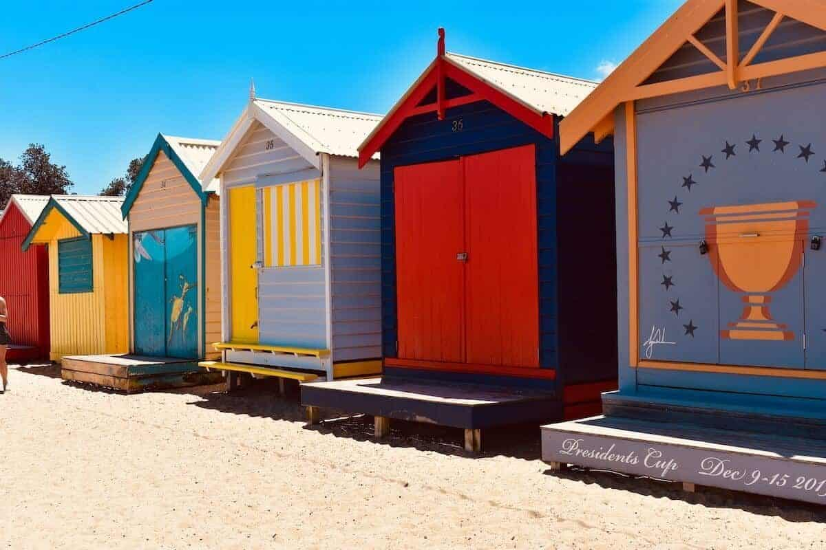 The Best Day Trips from Melbourne & Weekend Getaways in Victoria Cover Photo - Close up of 4 multi coloured bathing boxes on the beach