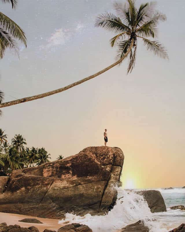 Image of Wijaya Beach - ocean on the right, on the left there is a large rock outcrop which has a singular palm tree hanging over on a 45 degree angle. A lone topless man with board shorts on is stood on the rock looking at the water