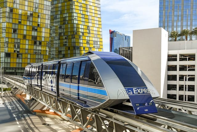 Aria Express Free Tram on the tracks in front of a yellow and silver tall building in Las Vegas