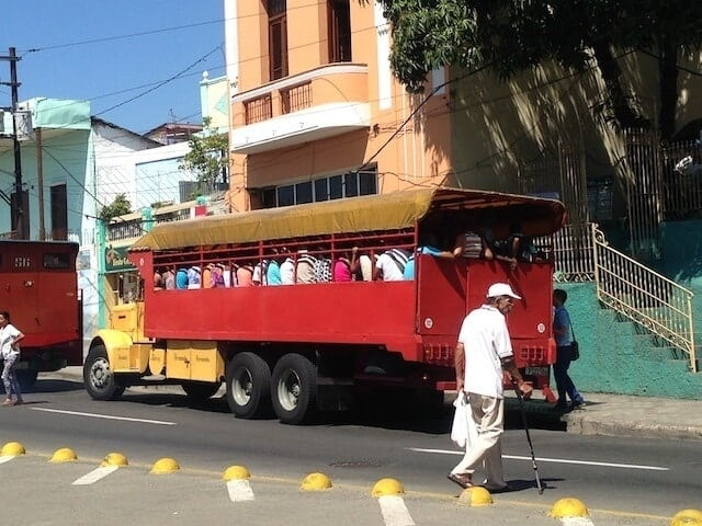 Red passenger trolley packed with people known as a Collectivo in Santaigo de Cuba parked in front of a light orange coloured building with a man dressed in white top and cream pants wearing a white baseball cap and using a walking cane to cross the road towards it